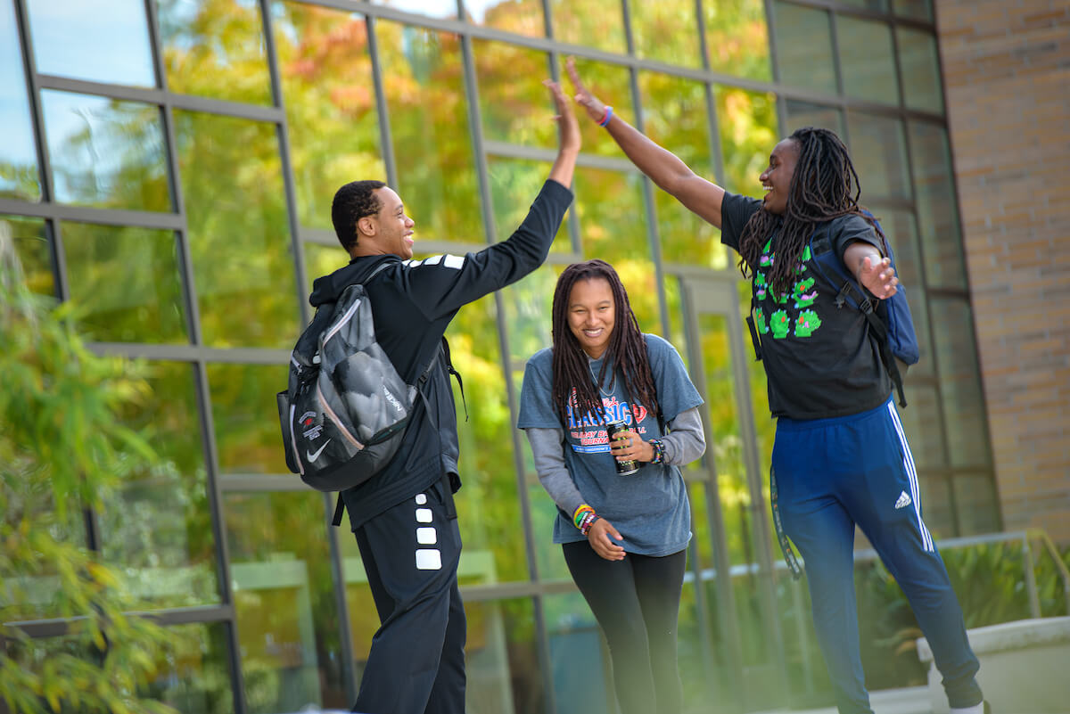 """students high-five on campus"""